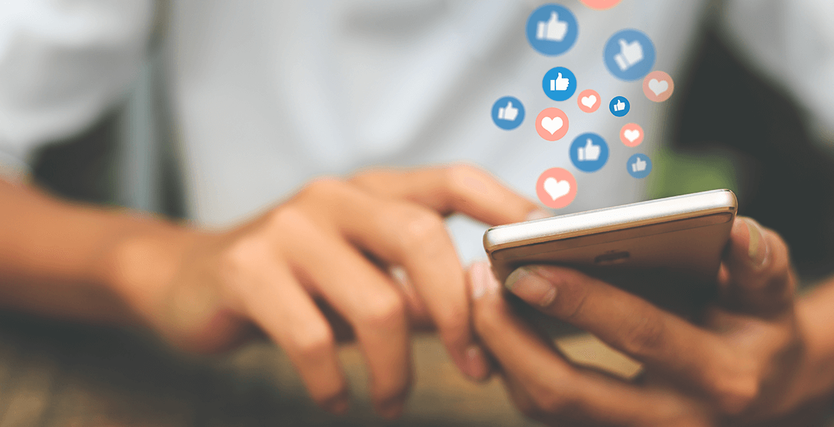 Man uses mobile device, liking and loving a brand's posts on social media